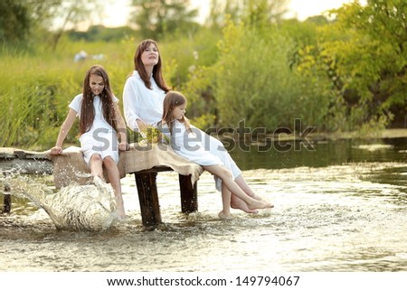 Family holiday mother and two daughters in the nature near the lake
