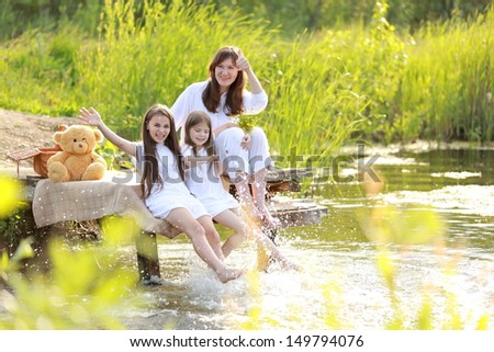 Family holiday mother and two daughters in the nature near the lake in the countryside