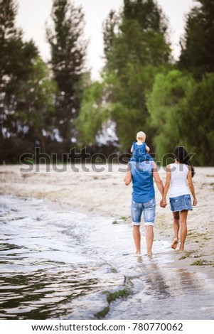 Family holiday near the sea. Two adults in jeans clothes with a child in their arms walk along the sandy beach from behind. #780770062