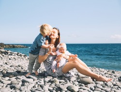 Family holiday on Tenerife, Spain. Mother with children outdoors on ocean. Portrait travel tourists - mom with kids. Positive human emotions, active lifestyles. Happy young family on sea beach