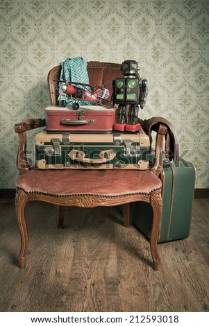 Family holiday packing with vintage suitcases and toys on elegant red velvet armchair.