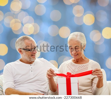 family, holidays, christmas, age and people concept - happy senior couple with gift box over blue lights background