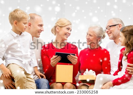 family, holidays, christmas, technology and people concept - smiling family with gift box and tablet pc computer sitting on couch at home