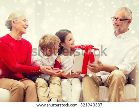 family, holidays, generation, christmas and people concept - smiling grandparents and grandchildren with gift box sitting on couch at home