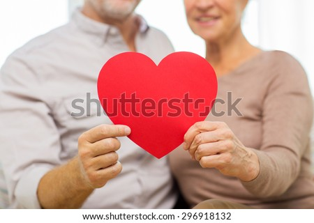 family, holidays, valentines day, age and people concept - close up of happy senior couple holding big red paper heart shape cutout at home