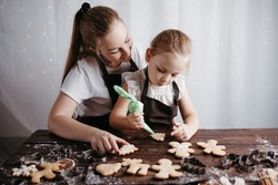 Family home bakery, cooking traditional festive sweets. Christmas and New Year celebration traditions. Mother and daughter decorating Christmas gingerbread cookies