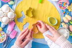 Family homemade holiday Easter pastry concept. baking background with mom and daughter child hands, flatlay top view. With dough, cupcake forms, cookie cutters and sugar sprinkles, ingredients
