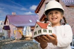 Family house concept - Outdoor portrait of little constructor girl with house model