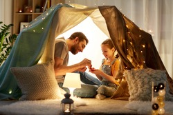 family, hygge and people concept - happy father and little daughter playing tea party in kids tent at night at home