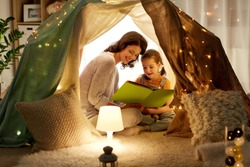 family, hygge and people concept - happy mother and little daughter reading book in kids tent at night at home