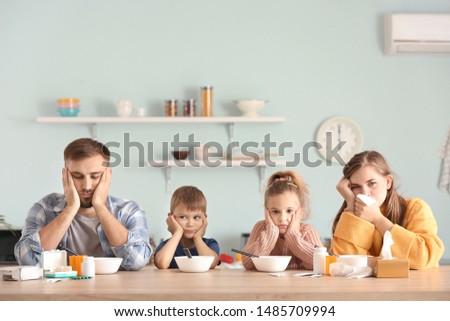 Family ill with flu sitting in kitchen