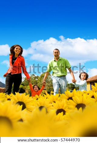 Family in a field of beautiful yellow sunflowers with a blue sky on the background