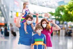 Family in airport in face mask. Virus outbreak. Coronavirus and flu pandemic. Safe travel with young child and baby. Mother, father and kids boarding airplane in surgical masks.