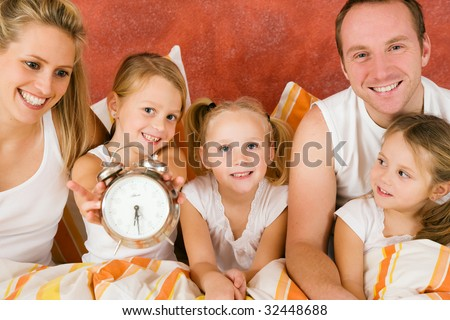 Family in bed in the morning, on child holding a clock â?? metaphor for getting up to enjoy the day