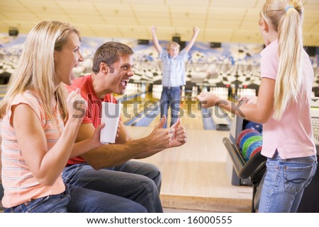 Family in bowling alley cheering and smiling