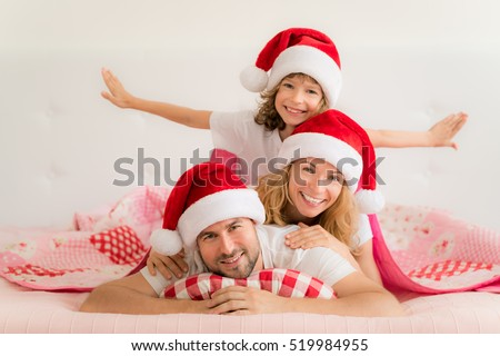 Family in Christmas Santa hats lying on bed. Mother; father and baby having fun in bedroom. People relaxing at home. Winter holiday Xmas and New Year concept
