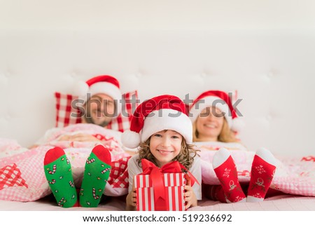 Family in Christmas Santa hats lying on bed. Mother; father and child having fun in bedroom. People relaxing at home. Kid holding gift box. Winter holiday Xmas and New Year concept