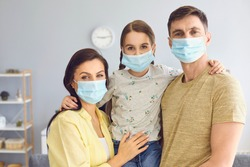 Family in medical masks on the face looks at the camera while standing in the room at home.