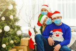 family in protective masks quarantined. Normal life with coronavirus. Lifestyle COVID-19. Quarantine virus protection. christmas