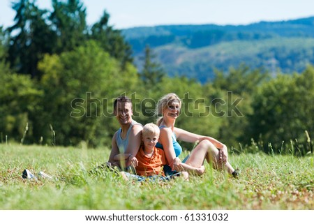 Family in sport clothes sitting on meadow in beautiful landscape, presumably they are resting in between exercises