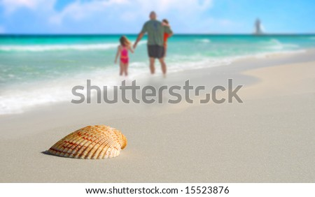 Family in surf by Pretty seashell on beach with sailboat in distance