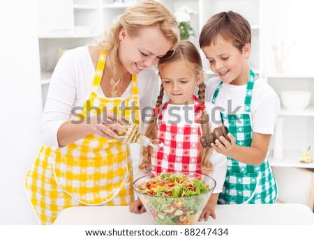 Family in the kitchen seasoning the fresh vegetables salad