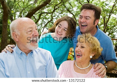 Family in the park, laughing at a joke told by the grandfather. - stock photo