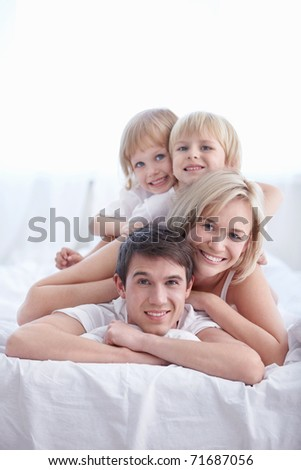 Family in their pajamas on the bed in the bedroom