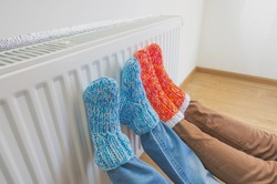 Family in warm knitted woolen socks near a home heater in cold winter time. The symbolic image of the heating season at home. Part of body, selective focus.