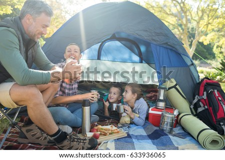 Family interacting while having snacks outside the tent at campsite