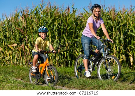 Family is cycling on their bicycles in summer - here mother with son