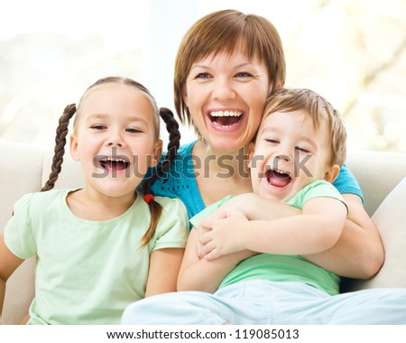 Family is having fun while sitting on a couch - stock photo