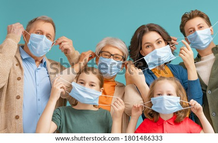 Family is wearing facemasks during coronavirus and flu outbreak. Virus and illness protection, quarantine. COVID-2019. Taking on or taking off masks. People on teal wall background.