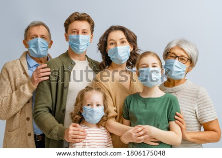 Family is wearing facemasks during coronavirus and flu outbreak. Virus and illness protection, quarantine. COVID-2019. Taking on or taking off masks. People on white wall background.