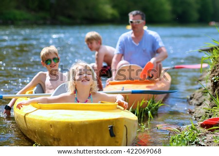 Family kayaking on the river. Active father with children, two teenage boys and little girl, having fun together enjoying adventurous experience with kayak on a sunny day during summer vacation