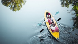 Family kayaking together in river.Tourists kayakers woman,man and child touring canoeing in a lake on a summer day.Back view.Summer family travel vacation concept. Active rest, water sports