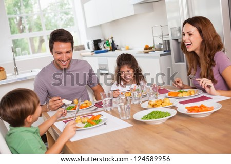 Family laughing around a good meal in kitchen