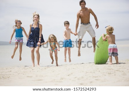 Family leaping into air at beach