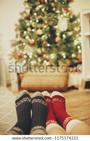 family legs in stylish festive socks on background of golden beautiful christmas tree with lights in festive room. relax time together. cozy winter holidays. warm atmospheric moment