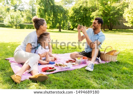 family, leisure and people concept - father taking picture of happy mother with two little sons by smartphone on picnic at summer park