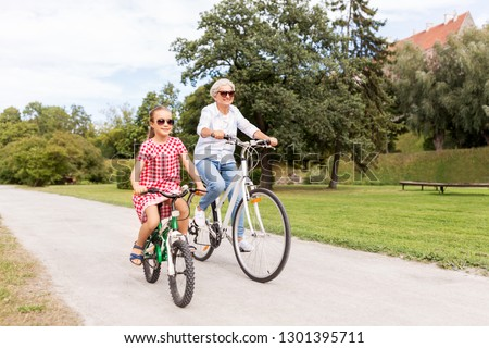 family, leisure and people concept - happy grandmother and granddaughter riding bicycles at summer park #1301395711