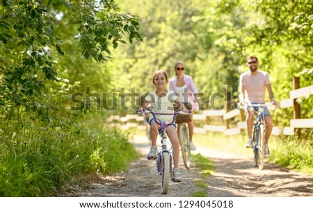 family, leisure and people concept - happy mother, father and little daughter riding bicycles in summer park