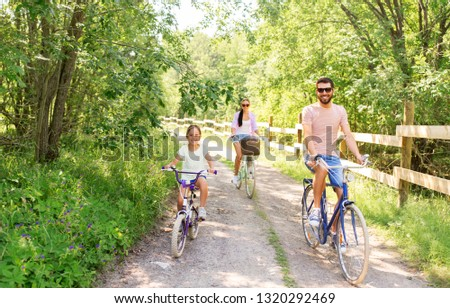 family, leisure and people concept - happy mother, father and little daughter with bicycles in summer park