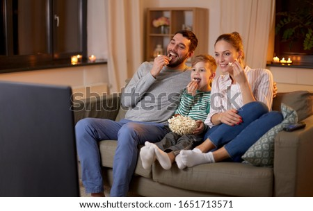 family, leisure and people concept - happy smiling father, mother and little son watching tv and eating popcorn at home at night
