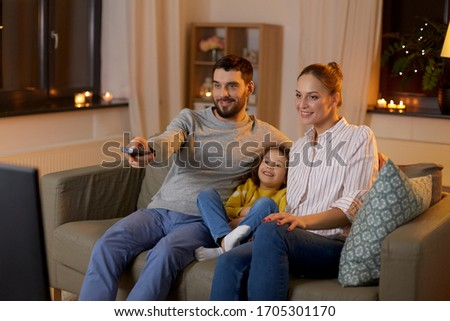 family, leisure and people concept - happy smiling father with remote control, mother and little daughter watching tv at home at night Foto stock ©