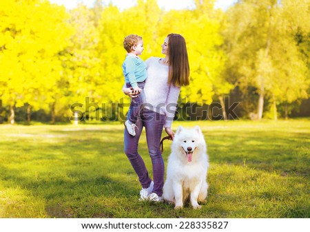 Family, leisure and people concept - mother and child having fun walking with dog in the park