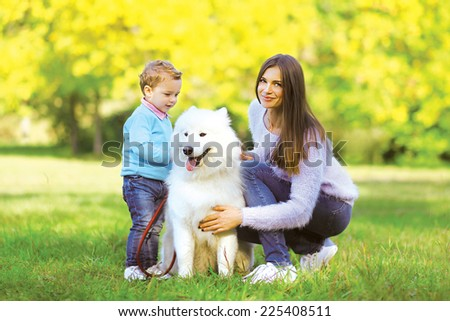 Family, leisure and people concept - mother and child walking with dog in the park