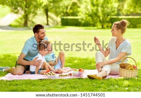 family, leisure and people concept - mother taking picture of happy father with two little sons by smartphone on picnic at summer park