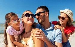 family, leisure and people concept - portrait of happy mother, father and two daughters in sunglasses on summer beach