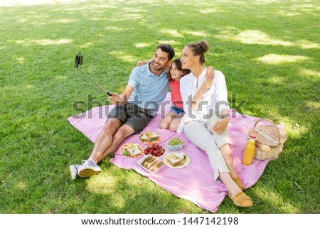 family, leisure and technology concept - happy mother, father and daughter having picnic and taking picture by smartphone on selfie stick at summer park